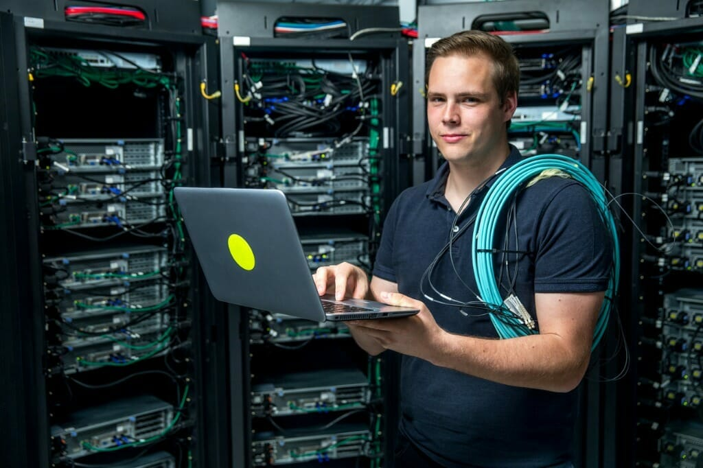 IT Professionals - an open letter - IT worker on laptop in front of data stack