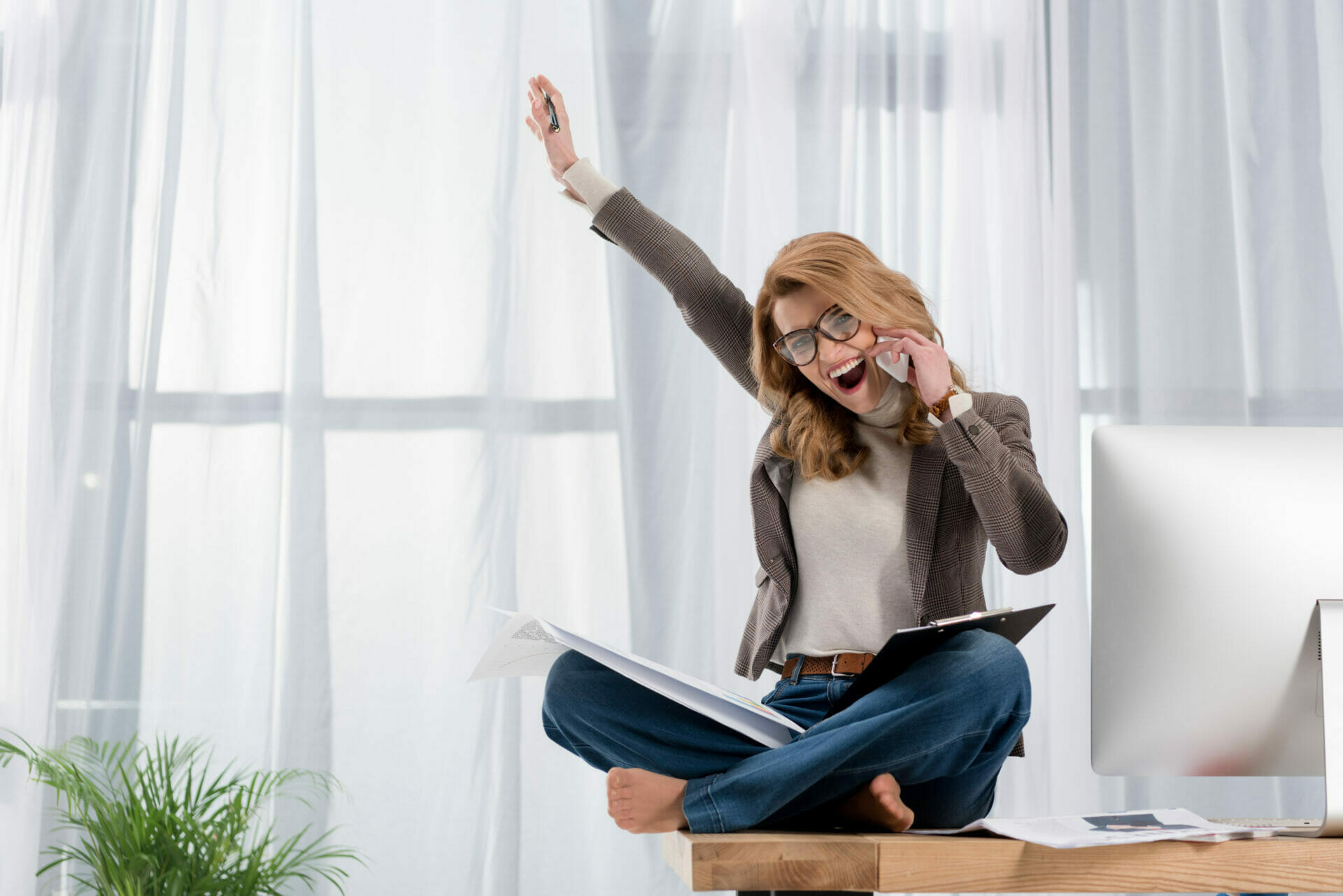 happy businesswoman with papers talking on smartphone while sitting on table in office - workplace flexibility